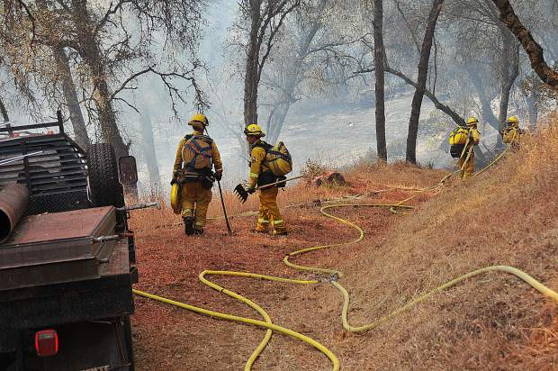 Cal Fire firefighters hold a flank of the Dove Fire during Wednesday's vegetation fire in western Nevada County.