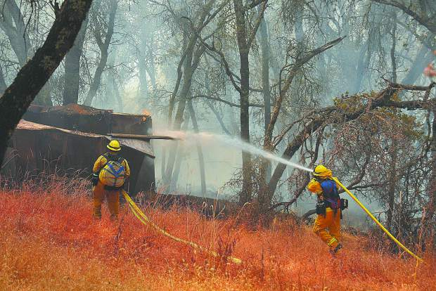 A pair of Cal Fire firefighters help to secure a flank of a 4 to 6 acre vegetation fire that threatened homes in the Dove Road region of western Nevada County Wednesday afternoon. Though a few outbuildings burned, the dwelling units in the area were saved.