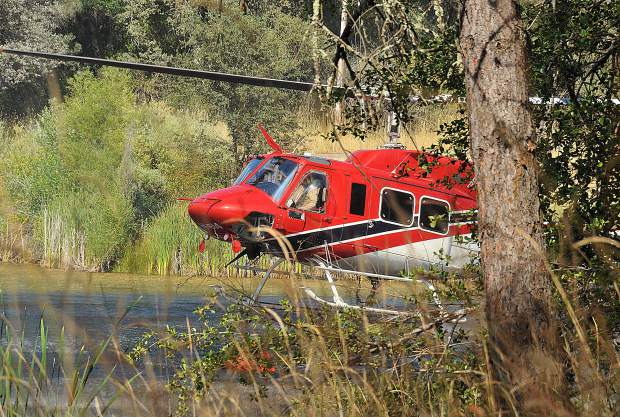 White Cloud Helicopter 514 dips into a pond to refill its drop bucket while working to protect homes in the Dove Road region of Western Nevada County Wednesday.