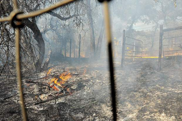 Smoke filled the air as the remnants of outbuildings burned along Dove Road in western Nevada County.