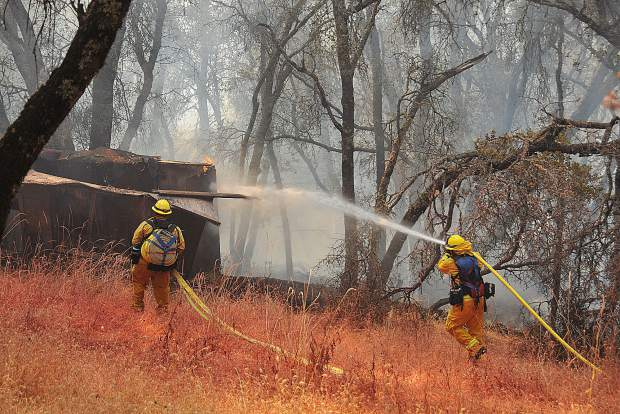 A pair of Cal Fire firefighters help to secure a flank of a 4- to 6-acre vegetation fire that threatened homes in the Dove Road region of western Nevada County Wednesday afternoon. Though a few outbuildings burned, the dwelling units in the area were saved.