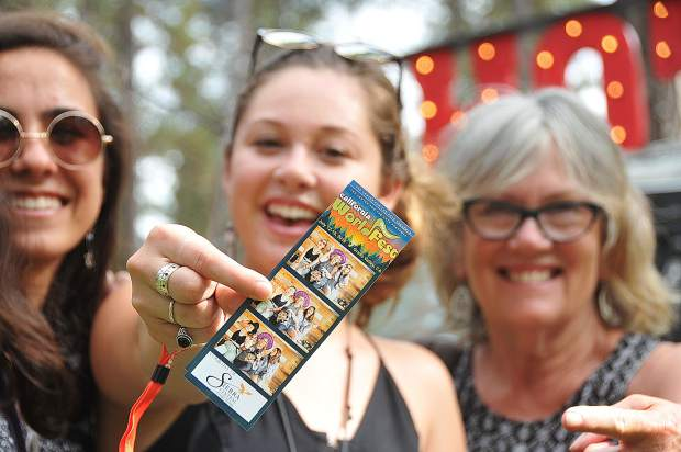 First time WorldFest campers Sydney Mangat, Natalie Pangilinan, and Patty Liron pose with their photo booth photos taken at WorldFest Friday at the Nevada County Fairgrounds.