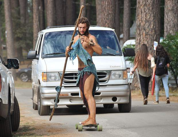 A long boarding man who calls himself Brother Bear, utilizes a long stick to propel himself through the WorldFest campground Friday.