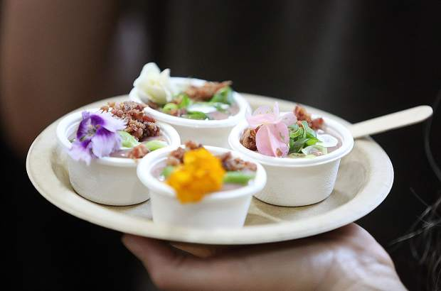 A plate full of Wild Eye Pub's loaded Vichyssoise, featuring edible flowers, is carried by a Bounty of the County patron during Thursday's event.
