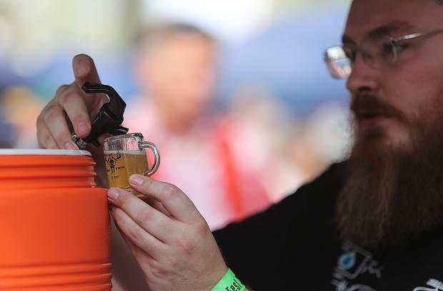 A home brewer pours his craft beer into one of the mini mugs given to Sierra BrewFest patrons.