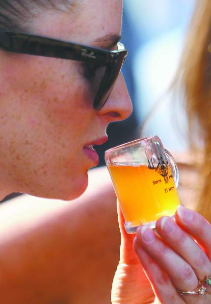 Grass Valley's Nicole Comendant readies to take a sip of a Belgian style white beer with tart cherries brewed by 26 year local brewer Steven Solik during the Music in the Mountains annual Sierra Brewfest fundraising event.