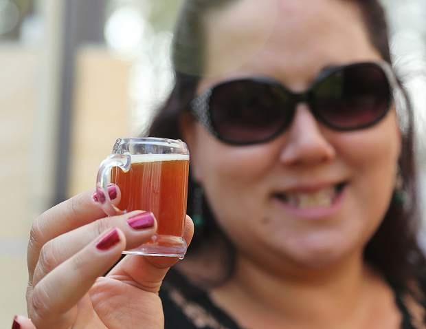 A Sierra BrewFest patron smiles as she holds her miniature mug of beer.