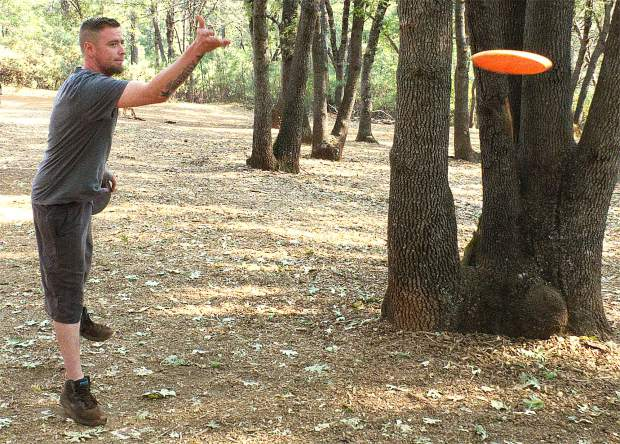 Nick Evans throws his disc toward the wire basket during a round at Condon Park Saturday.