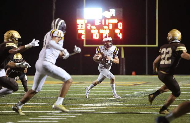 Nevada Union quarterback Dawson Fay (5) looks for an open player to pass the ball to during the Miners' 4th quarter drive to the end zone that netted no points during Friday night's varsity matchup at the Yuba City Honkers.