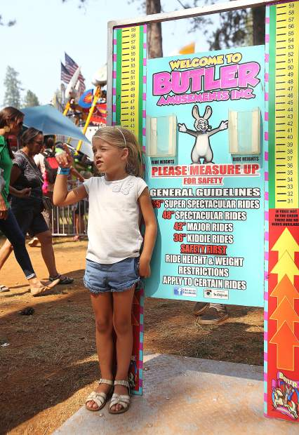 Five-year-old Quinn McClendon sizes herself up on the ride height chart while her mother tries to talk her out of the