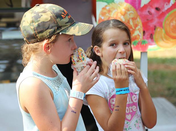 Alivia Raney and Aniya Davis bite into ice cream cookie-wiches from Three Ginger's Bakery Wednesday afternoon along Treat Street at the Nevada County Fairgrounds.