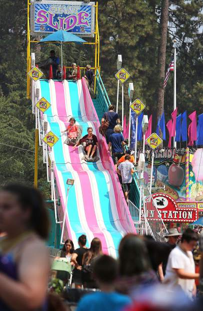 Fair-goers ride the Giant Slide Wednesday during the opening day of the fair.