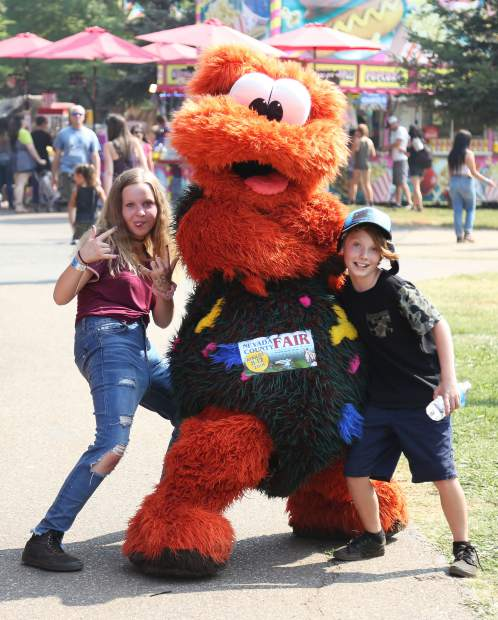 A pair of youngsters pose for a picture with one of the Fritters Critters walking around the Nevada County Fairgrounds on opening day. The Fritters are new to the fair this year.