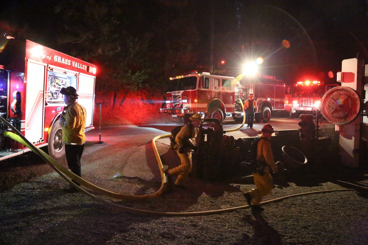 Grass Valley firefighters access the vegetation fire from the North Star Mining Museum at the intersection of Allison Ranch Road and Freeman Lane Friday evening after an apparent electrical transformer blew and also caused a power outage at the Nevada County Fairgrounds.