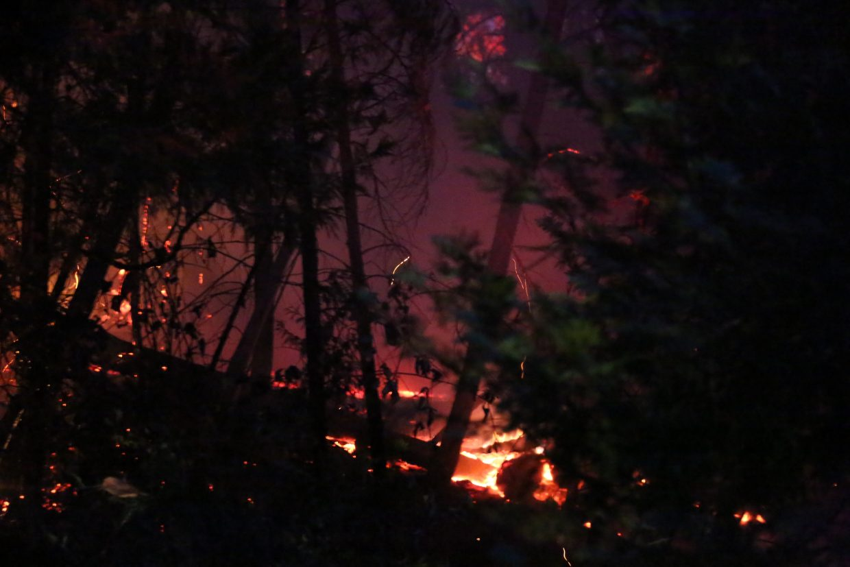 Embers glow as Grass Valley firefighters get the vegetation fire from the Fair Incident out Friday night across from the North Star Mining Museum.