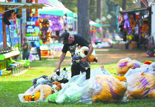 A Nevada County Fair Midway worker stocks one of the many games with stuffed animal prizes Tuesday before Wednesday's opening of the fair.