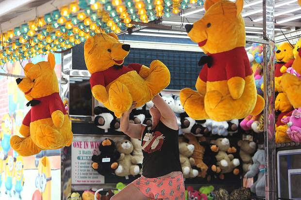Heather Greene hangs up a Winnie the Pooh stuffed animal at her game station during Tuesday's preparation of the Nevada County Fair in Grass Valley.