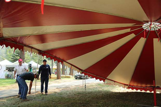 Don Tucker, Corey Macgill, and Bulmaro Bribiesca set up the red and white tent of Tucker's Pony Rides Tuesday at the Nevada County Fairgrounds.