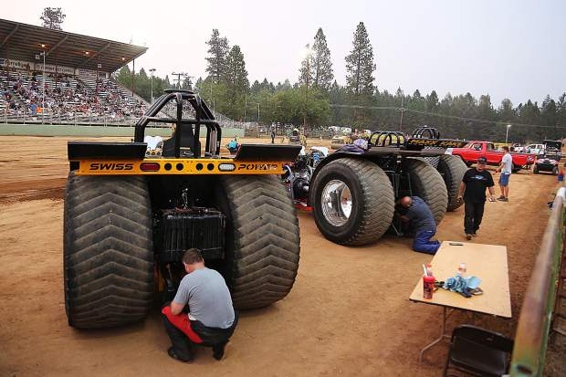 Drivers of the multi-engined Outlaw Unlimited class ready their machines for their sled pull down the arena Thursday evening at the fair.