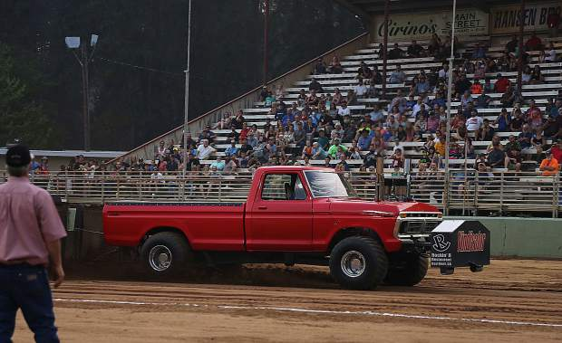 A super modified 4-wheel drive truck named Vindicator pulls the sled down the arena at the Nevada County Fairgrounds.