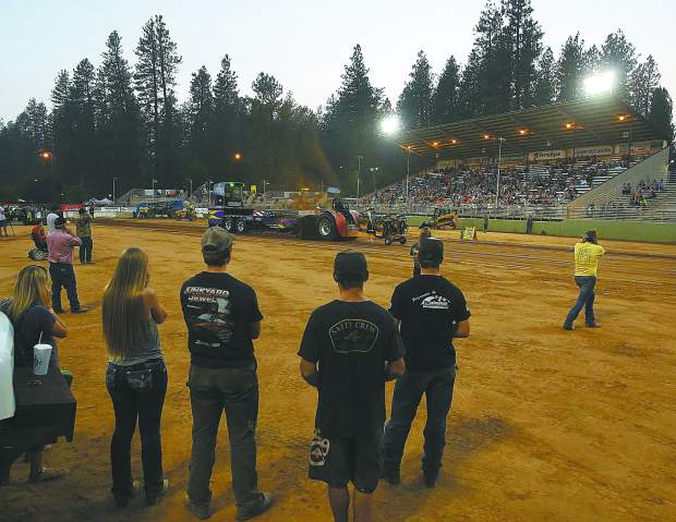 Pit crew members of the All Star All American Truck and Tractor Pull watch as the multi-engine Outlaw Unlimited tractor named Swiss Power, barrels down the arena pulling a weighted sled Thursday evening at the Nevada County Fair. This is the first year that the fair has featured a truck and tractor pull.