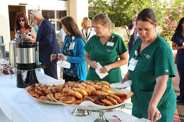 Hospital staff enjoy doughnuts, coffee and other treats following Wednesday morning's ribbon cutting ceremony.
