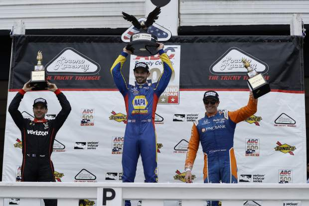 Alexander Rossi, center, celebrates after winning the IndyCar auto race at Pocono Raceway, Sunday in Long Pond, Pa.