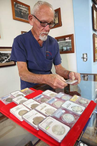 John Englehardt looks through a collection of silver dollars that are for sale at the downtown Grass Valley Sierra Gold and Coin store.