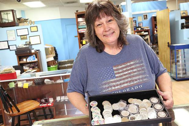 Deb, who specializes in foreign coins, shows off some of Sierra Gold & Coin's items for sale at her downtown Grass Valley shop.