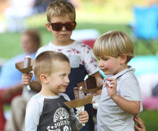 Three year old Fox, and brothers River and Henry Atkinson, enjoy their Lazy Dog ice-creams during Saturday's Miners Picnic.