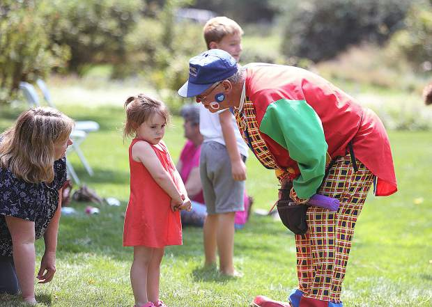 Ray Ray the clown looks to cheer up a reluctant three year old Anna Baptiste, with a balloon flower during Saturday's Miner's Picnic on the grounds of the Empire Mine State Historic Park.