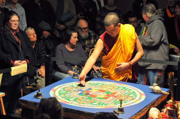 A Tibetan Buddhist monk explains some of the meaning behind the symbols and images in the completed sand mandala at St. Joseph's Cultural Center in Grass Valley. The monks held their closing ceremony for their two month long journey through the Sierra Nevada and two week stay in Grass Valley.