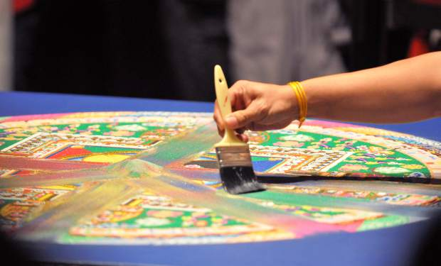 A monk sweeps a portion of the Grass Valley sand mandala.