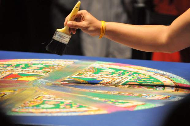 A monk sweeps a portion of the Grass Valley sand mandala. After giving away a portion of the mandala to those in attendance of the closing ceremony, the monks will drop the rest of the mandala into Deer Creek and Wolf Creek.