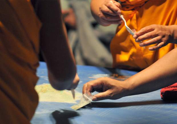 After sweeping up the mandala, small portions of the sand are placed into baggies and passed around the congregation. Placement of the sand onto the head of a recently deceased person is said to assist in that process.