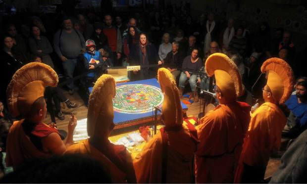 The five visiting Tibetan Buddhist monks sing and chant prayer over the finished sand mandala in front of a large crowd in attendance of their closing ceremony Saturday evening at St. Joseph's Cultural Center in Grass Valley. On Sunday morning the monks poured portions of the mandala into Deer Creek in Nevada City, and Wolf Creek in Grass Valley.