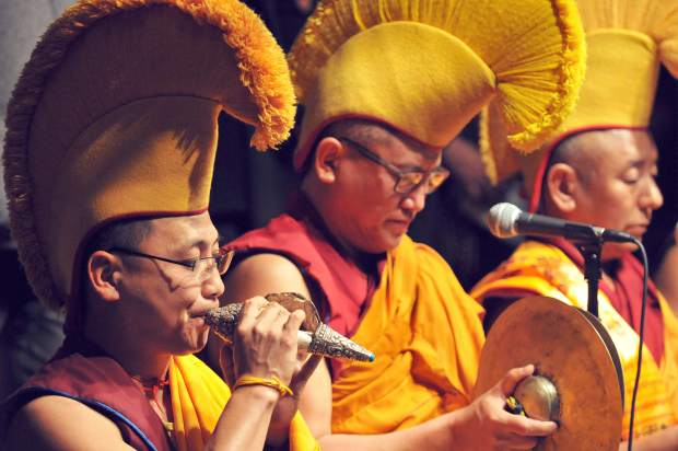 The monks use a variety of instruments, including conch shells, drums, cymbals, and bells, to send off their sand mandala.