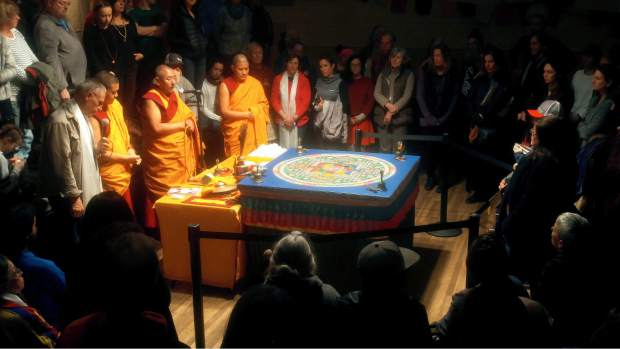 The five visiting Tibetan Monks chant prayers and song over their finished sand mandala Saturday evening at St. Joseph's Cultural Center in Grass Valley before dissolving the mandala into a pile of sand, some of which was distributed to everyone in attendance of the closing ceremony.