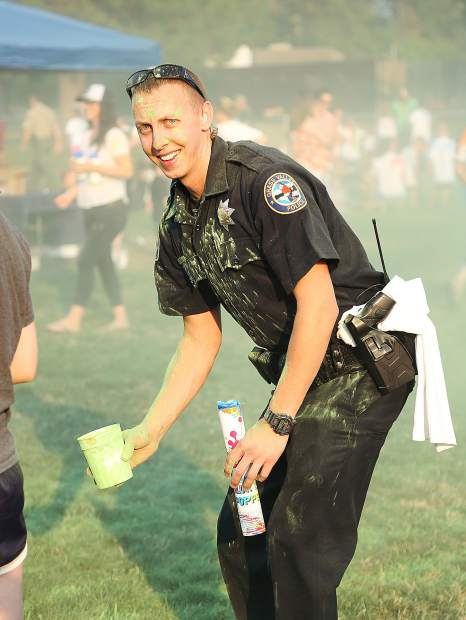 Grass Valley Cpl. Dennis Grube takes a moment to pause from his colored chalk tossing duties to offer a smile Tuesday evening at DeVere Mautino Park in Grass Valley where the dual Nevada City and Grass Valley National Night Out took place.