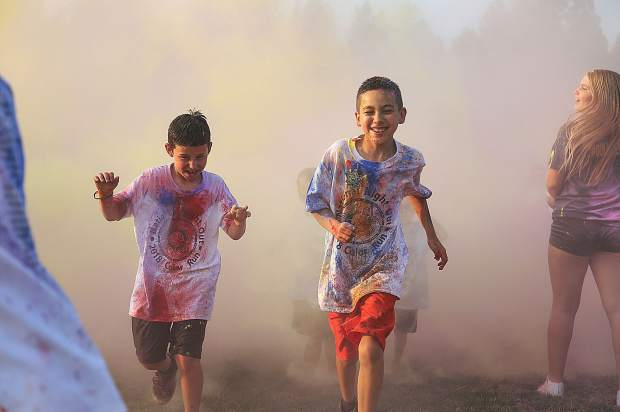 Elated faces emerge from the colors during Tuesday's color run portion of the western Nevada County National Night Out.