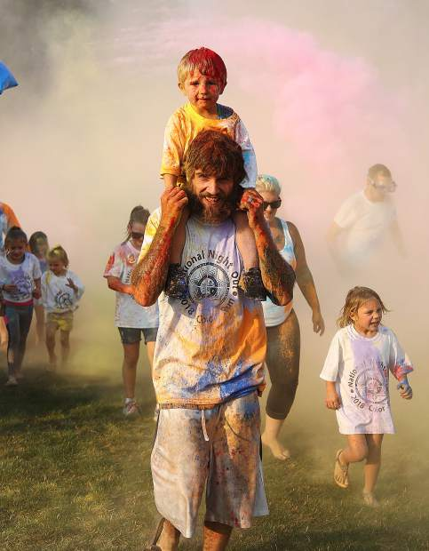 National Night Out participants emerge from the color run in a rainbow colored array.