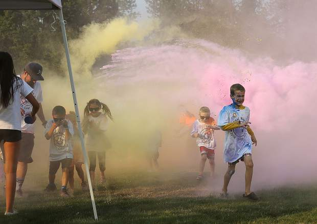 Youngsters utilize sunglasses to shield their eyes as they run through clouds of colored chalk during Tuesday's color run portion of National Night Out.