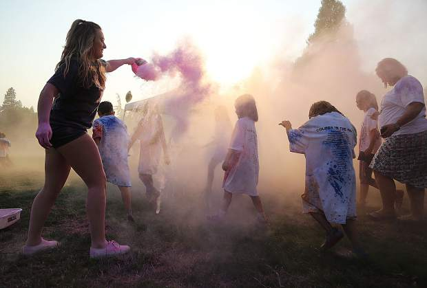 Members of the Nevada Union cheerleaders spread pink colored chalk into the air while National Night Out participants run through.