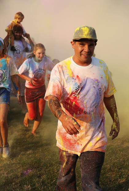 Faces emerge from the color run in an array of rainbow colored chalk.