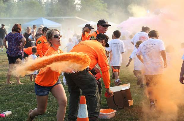 Nevada County Search and Rescue's Lindy Sexton tosses a glob of orange colored chalk at a group of color runners.