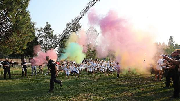 Grass Valley Chief of Police Alex Gammelgard leads the children at the beginning of the color run portion of Tuesday's National Night Out.
