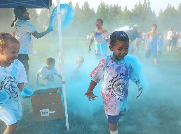 Children make their way through the blue colored chalk cloud.