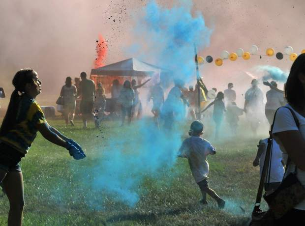 Nevada County youth run through colored clouds during Tuesday evening's National Night Out festivities at Nevada City's Pioneer Park.