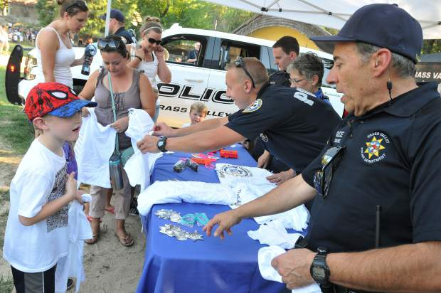 FILE — Gerard Tassone (right) offers six-year-old Nevada City youth Nick Leach an honorary Nevada City Police Officer badge while shirts and other goodies are given to the children prior to the popular color run in 2017.