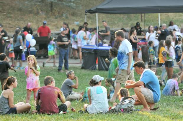 Western Nevada County community members enjoy hotdogs and cold water in front of the band shell at Pioneer Park following the National Night Out color run.